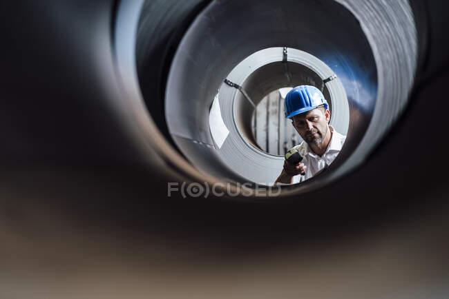 Hombre escaneando código de barras en rollos de acero en la industria - foto de stock