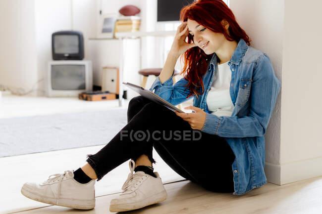 Mujer sonriente con la cabeza en las manos usando tableta digital mientras está sentada en el suelo en la oficina - foto de stock