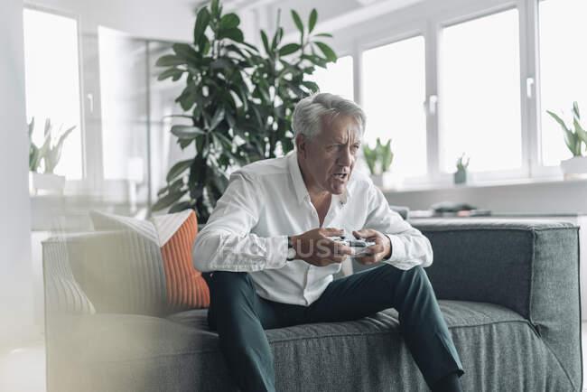 Uomo d'affari anziano che gioca al videogioco con concentrazione mentre è seduto sul divano in ufficio — Foto stock