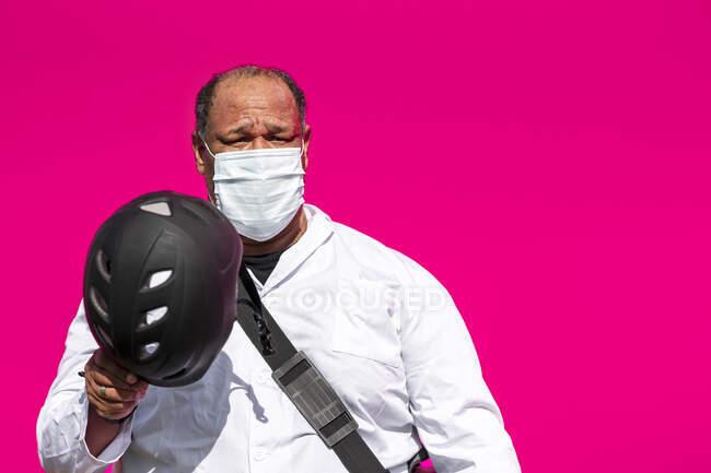 Hombre con máscara protectora que sostiene el casco mientras está de pie contra la pared rosa - foto de stock
