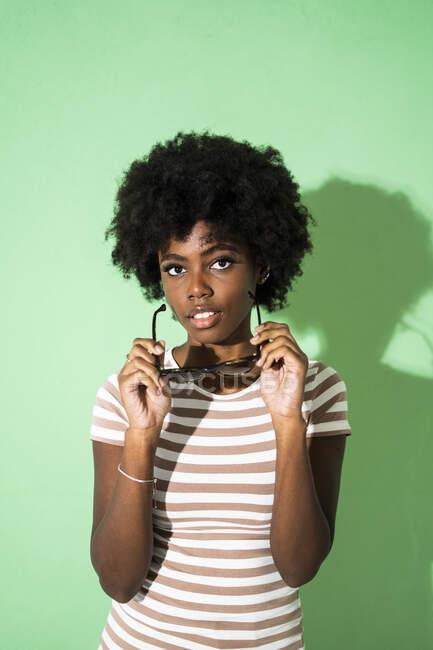 Молода жінка тримає сонцезахисні окуляри, стоячи навпроти зеленого фону. — стокове фото