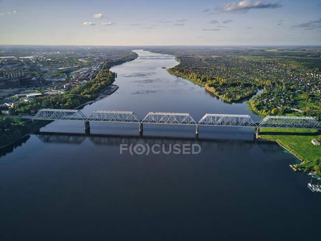 Vista aérea del puente ferroviario sobre el río Volga en la ciudad contra el cielo al atardecer - foto de stock