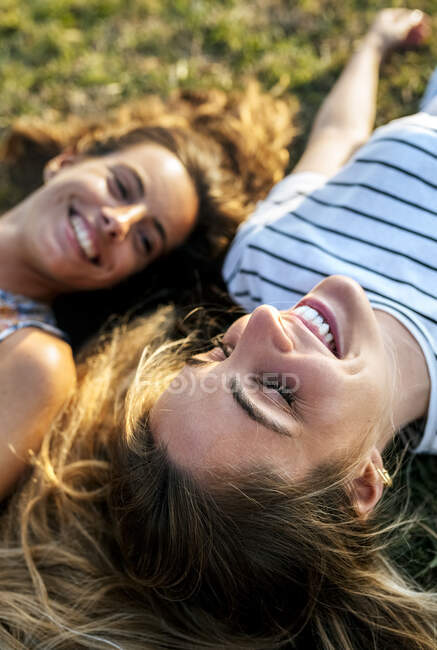 Smiling young woman relaxing with sister on field — Stock Photo