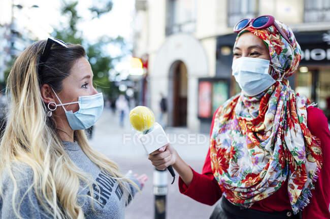 Periodista entrevistando a una mujer con micrófono en la ciudad durante COVID-19 - foto de stock