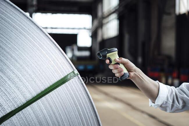 Código de barras de escaneo manual del hombre en rollos de acero en la industria - foto de stock