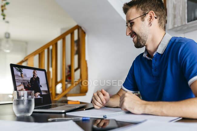 Усміхнений чоловік, який консультується з професором через відеодзвінок з ноутбука вдома. — стокове фото
