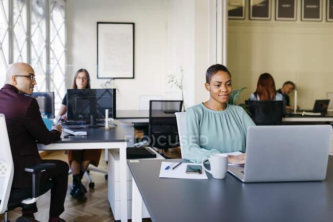 Femme d'affaires souriante travaillant sur un ordinateur portable au bureau — Photo de stock