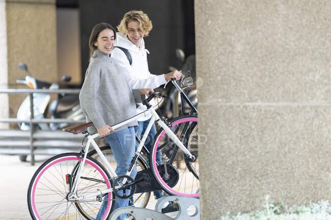 Amigos felices con bicicleta en el estacionamiento - foto de stock