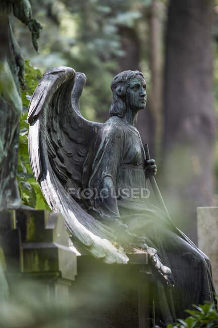 Estatua envejecida de ángel sentado al borde de la tumba en el cementerio - foto de stock
