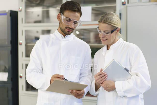 Jeune technicien masculin discutant sur presse-papiers avec une collègue blonde tenant une tablette numérique au laboratoire — Photo de stock