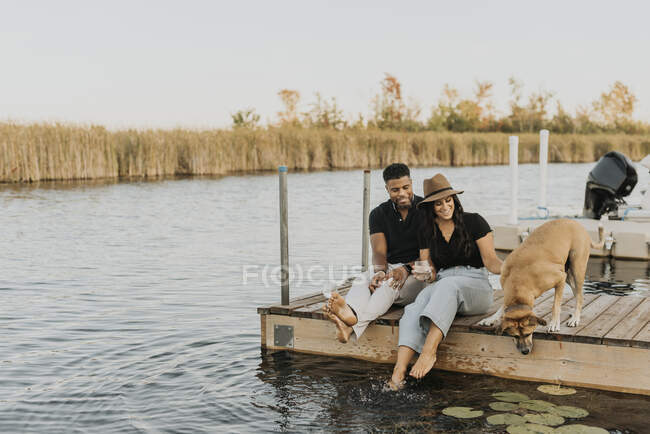 Smiling couple sitting with dog on pier — Stock Photo