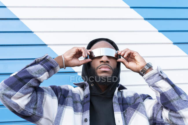 Young male rapper with arms raised wearing sunglasses against corrugated iron — Stock Photo