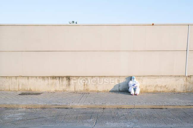 Медсестра в защитном костюме сидит на тропинке у стены — стоковое фото