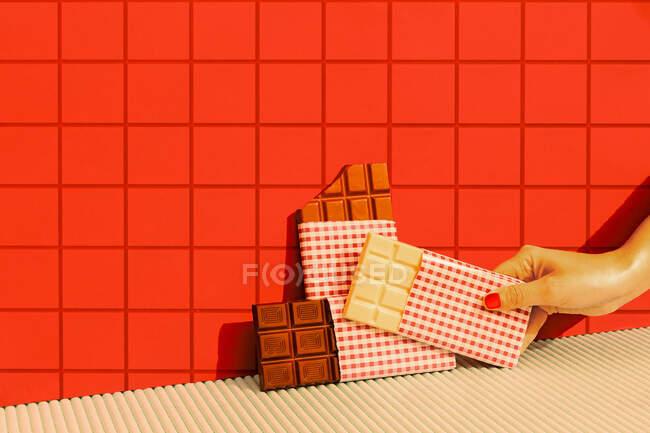 Mujer mano poner barra de chocolate contra la pared de baldosas rojas - foto de stock