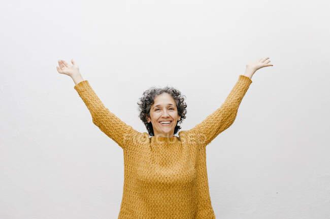 Donna felice in maglione arancione in piedi con le braccia sollevate contro la parete bianca — Foto stock