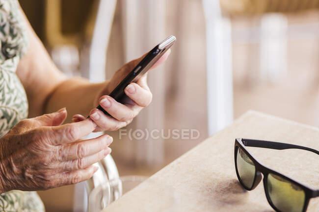 Senior mulher usando telefone celular enquanto sentado à mesa no café — Fotografia de Stock