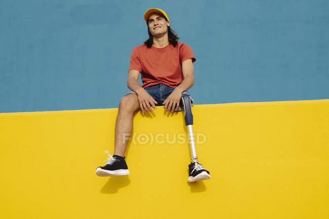 Спортсмен усміхається, сидячи на багатокольоровій стіні. — стокове фото