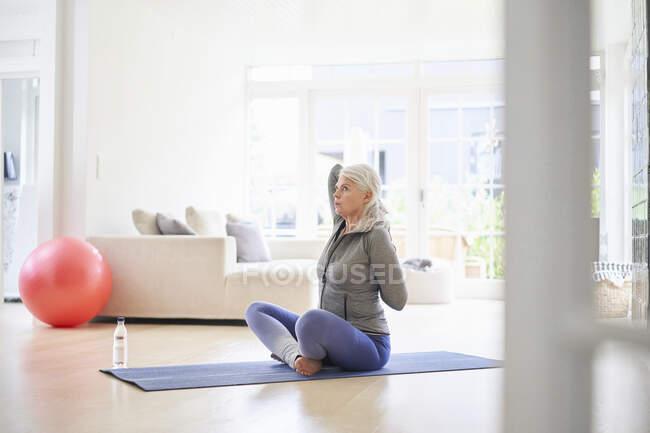 Mujer mayor haciendo ejercicio con las manos detrás en la sala de estar - foto de stock