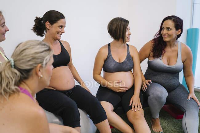 Группа беременных женщин разговаривает друг с другом в студии йоги — стоковое фото
