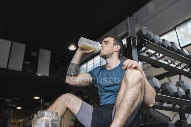 Male athlete drinking protein shake while sitting in gym — Stock Photo
