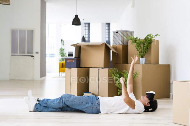 Молодой человек, лежащий в симуляторе виртуальной реальности в новом доме — стоковое фото