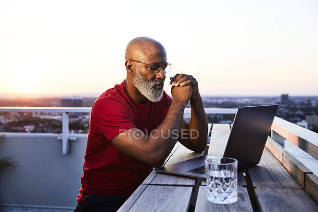 Mature bearded man looking at laptop while sitting on building terrace in city during sunset — Stock Photo