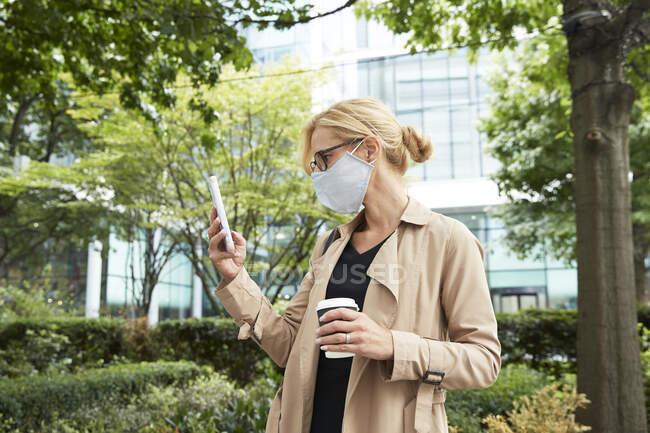 Жінка тримає чашку кави, користуючись мобільним телефоном у місті. — стокове фото