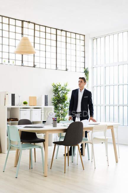Junge männliche Unternehmer schauen weg, während sie am Schreibtisch am Arbeitsplatz Strategien planen — Stockfoto