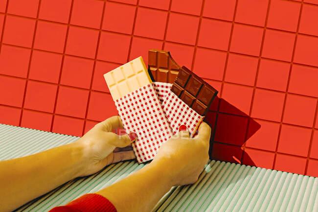 Manos de mujer sosteniendo barras de chocolate contra la pared de azulejos rojos - foto de stock