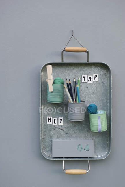 На стіні висять контейнери з металевим підносом. — стокове фото