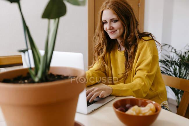 Donna sorridente che utilizza il computer portatile mentre seduto a casa — Foto stock