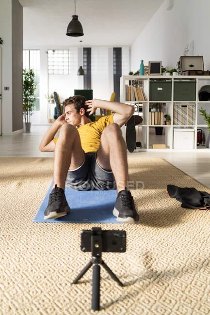 Entrenador de fitness con trípode que estira el ejercicio abdominal en la esterilla en casa - foto de stock