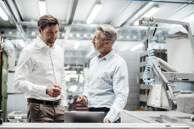 Maduro masculino engenheiros discutir sobre laptop na indústria de fabricação — Fotografia de Stock