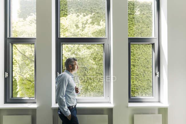 Empresário com as mãos nos bolsos olhando pela janela enquanto estava no escritório — Fotografia de Stock