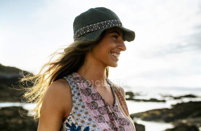 Joven alegre con sombrero mirando hacia otro lado mientras pasa el fin de semana en la playa - foto de stock