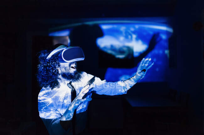 Playful man with virtual reality glasses standing in dark at home during pandemi — Stock Photo