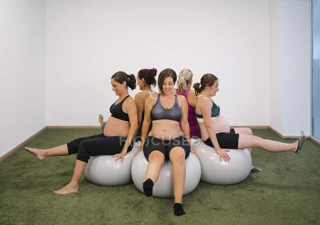 Беременная женщина сидит на фитнес-мяч в круглом круге с ногой вверх в студии йоги — стоковое фото