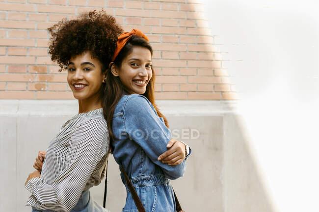 Усміхнені друзі, які стоять спиною проти стіни. — стокове фото