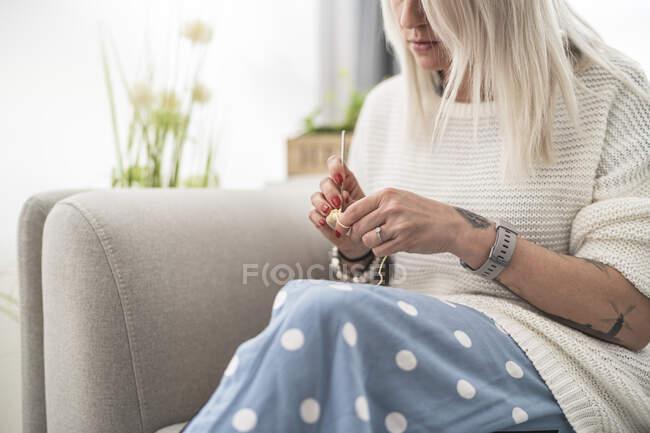 У дорослої жінки крохмаль пакунок під час сидіння на дивані вдома. — стокове фото