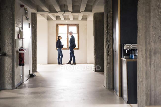 Gente de negocios hablando mientras están de pie junto a la ventana en la oficina - foto de stock