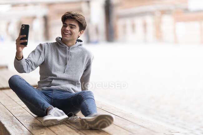 Giovane allegro prendere selfie mentre seduto sul tavolo di legno al caffè marciapiede in città — Foto stock