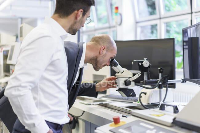Jeune technicien masculin debout par un homme d'affaires regardant au microscope au laboratoire — Photo de stock