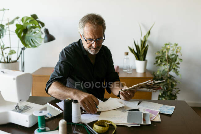 Diseñador de vestuario masculino mirando documentos mientras está sentado en la mesa en el estudio de trabajo - foto de stock