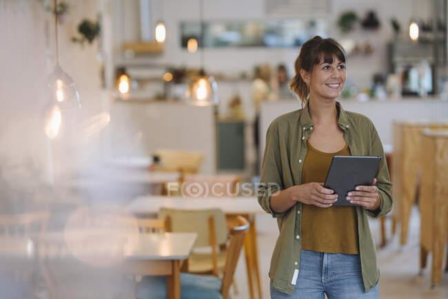 Усміхнена жінка-підприємець озирається, тримаючи цифровий таблетку стоячи в кафе. — стокове фото