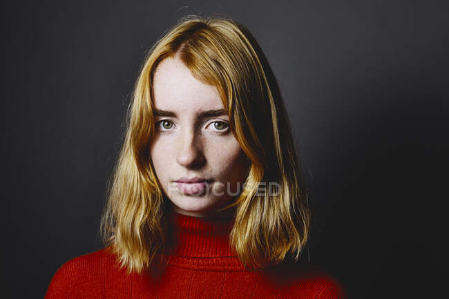 Blond teenage girl staring while standing against gray background — Stock Photo