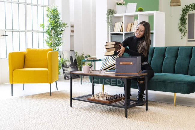 Улыбающаяся молодая женщина собирает книги в коробке на журнальном столике в квартире на чердаке — стоковое фото