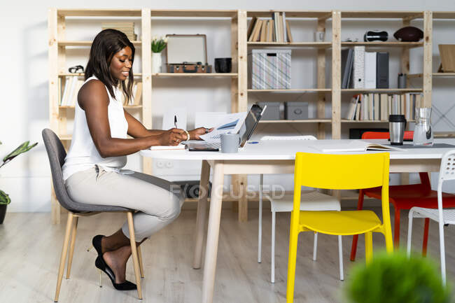 Businesswoman working while sitting by table at office — Stock Photo