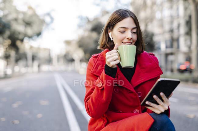 Усмішка молодої жінки в зимовій куртці з кавою під час користування цифровим планшетом на дорозі. — стокове фото