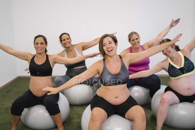 Счастливая беременная женщина с протянутыми руками сидит на фитнес-мяч — стоковое фото