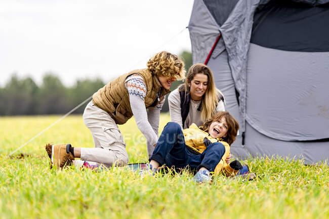 Tre fratelli che giocano sull'erba davanti alla tenda accampata — Foto stock